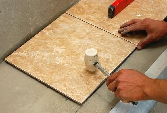 Установка плитки на нужный уровень с помощью молотка