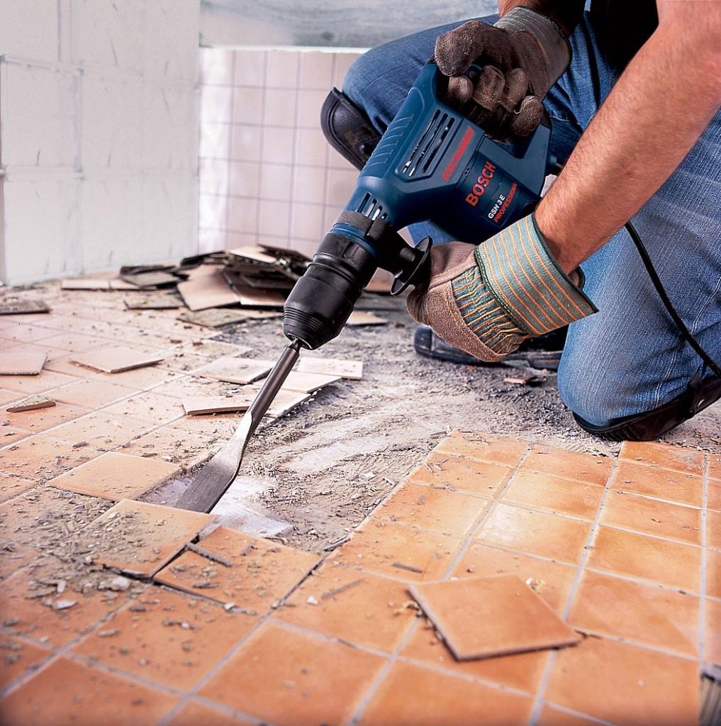 Мастер демонтирует плитку перфоратором