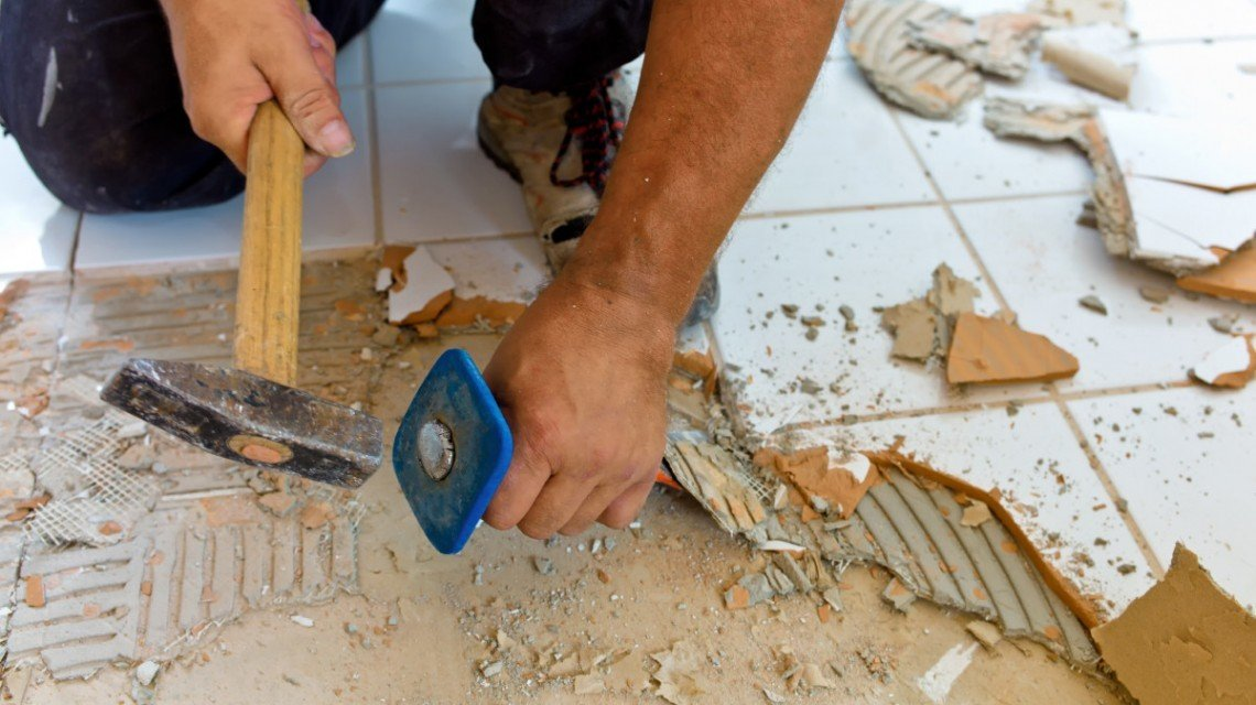 Каменщик демонтирует плитку