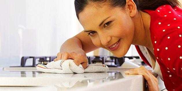 Женщина чистит столешницу
